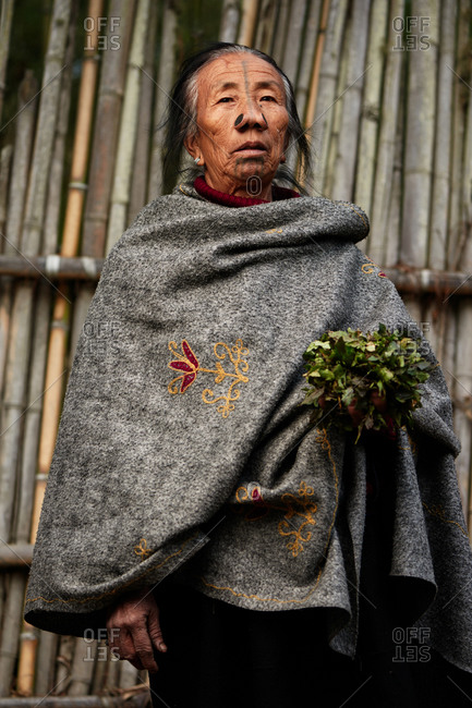Arunachal pradesh, India - January 30, 2016: Portrait of an Apatani woman standing in front of a bamboo wall