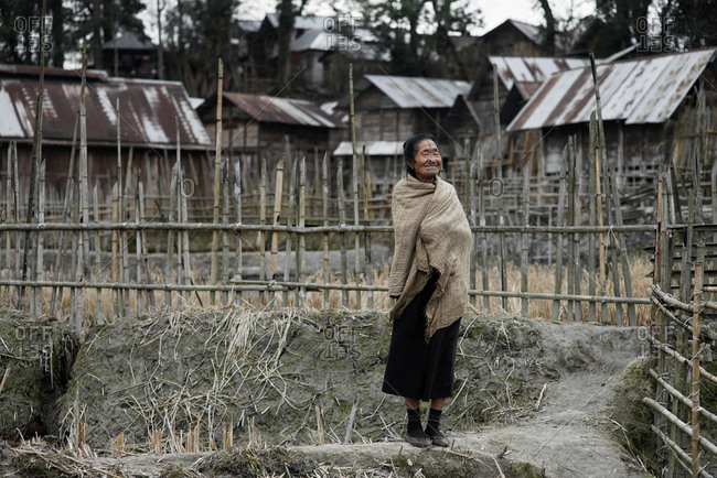 Arunachal pradesh, India - February 1, 2016: Portrait of an Apatani woman standing near a bamboo fence
