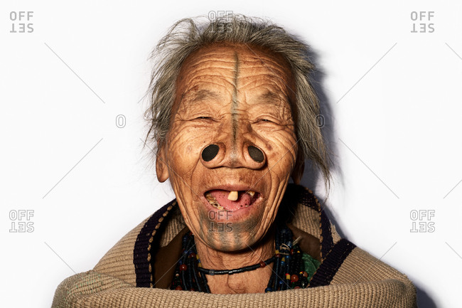 Arunachal pradesh, India - February 1, 2016: Portrait of an Apatani woman with traditional bamboo discs in her nose on a white seamless background