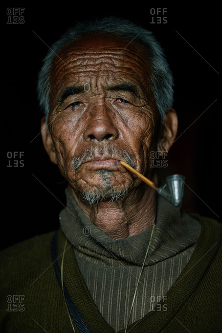 Arunachal pradesh, India - January 30, 2016: Portrait of an Apatani man smoking a pipe against a dark background