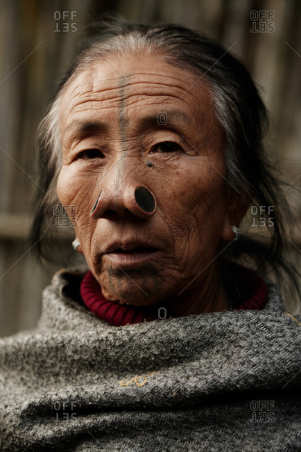 Arunachal pradesh, India - January 30, 2016: Portrait of an Apatani woman standing near a bamboo wall