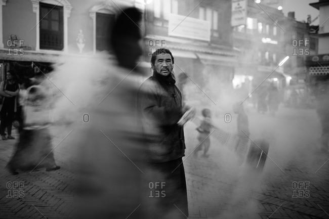 Kathmandu, Nepal - November 15, 2013: Man swinging incense in street in Kathmandu, Nepal