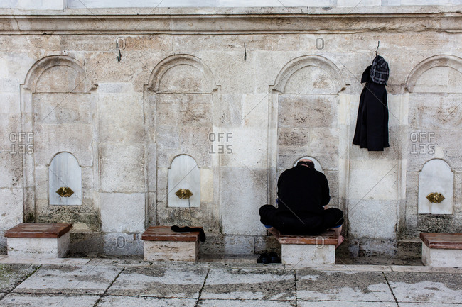 Man seated at washing spigots at the Blue Mosque in Istanbul, Turkey