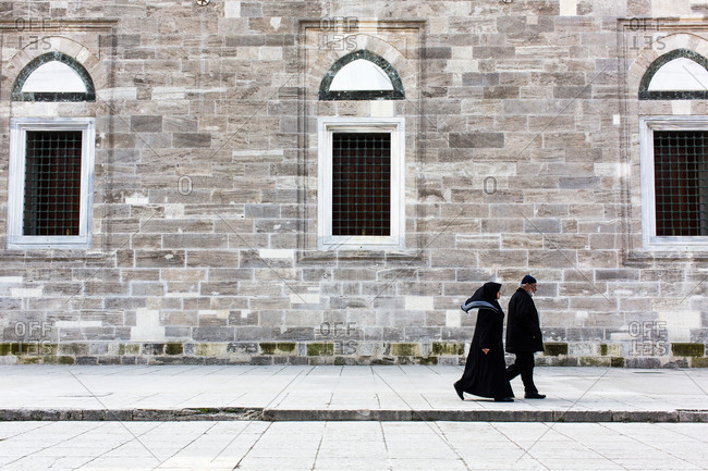 Istanbul, Turkey - January 11, 2014: Elderly man and woman dressed in black walk on street in Istanbul, Turkey