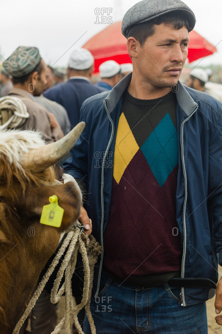 Kashgar, China - May 10, 2015: Portrait of a man with cow at auction