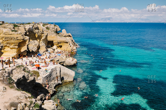 Palermo, Italy - August 20, 2015: People climbing down rock to get to the sea in Italy