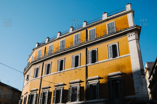 Sunlit apartment building from street level in Italy
