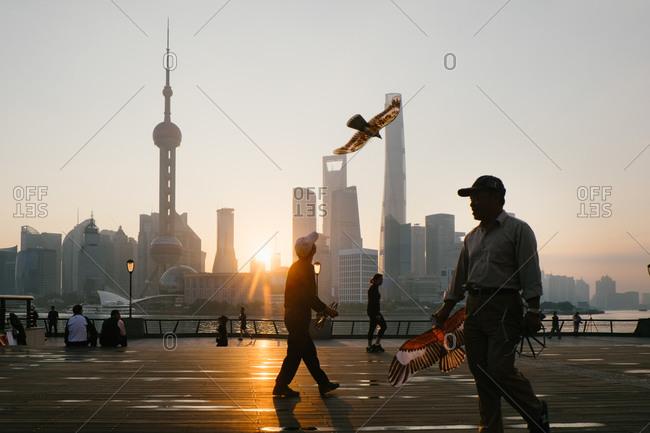 Shanghai, China - October 19, 2015: Men flying bird kites at park waterfront park in Shanghai, China