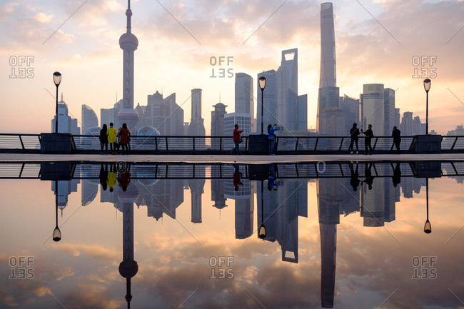 Shanghai cityscape reflected in water at sunset