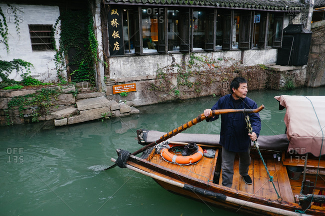 ZhouZhuang, China - December 1, 2015: Boat driver drives past restaurant building on canal, China
