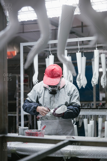 Man working on mannequin arms in factory
