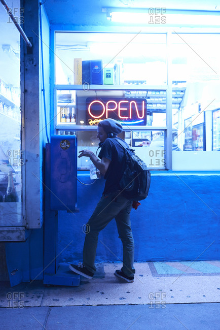 12/09/2014, Miami, Florida, USA: Young man on the phone at a pay phone at night