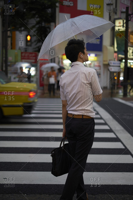 07.24.2013, Tokyo, Japan: Japanese with umbrella on a crosswalk