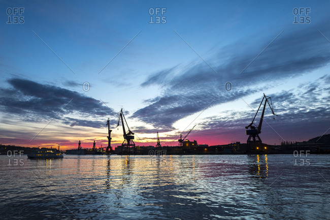 Silhouette of cranes on the shoreline Gothenburg, Sweden at sunset