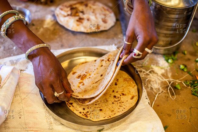 Woman preparing flatbread, India