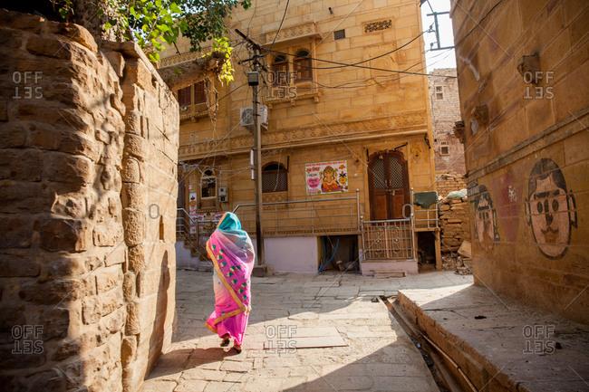 November 25, 2015: Woman walking in Indian small street