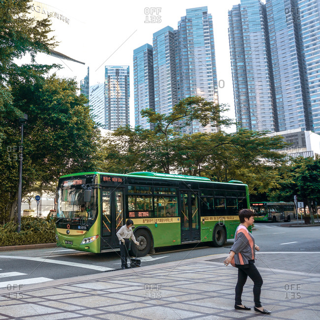 August 3, 2014: Woman sweeping near bus in city