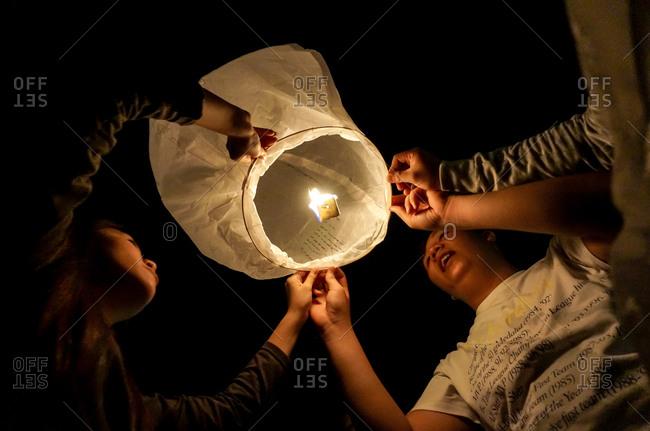 June 26, 2015: People lighting a sky lantern