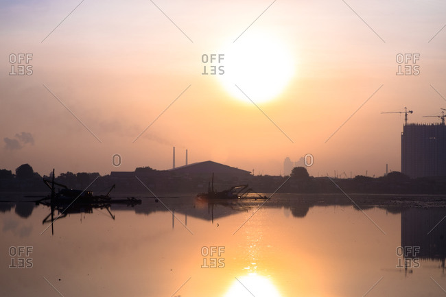 Buildings reflected in sunlit lake