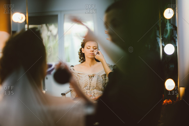Makeup artist applying makeup on bride