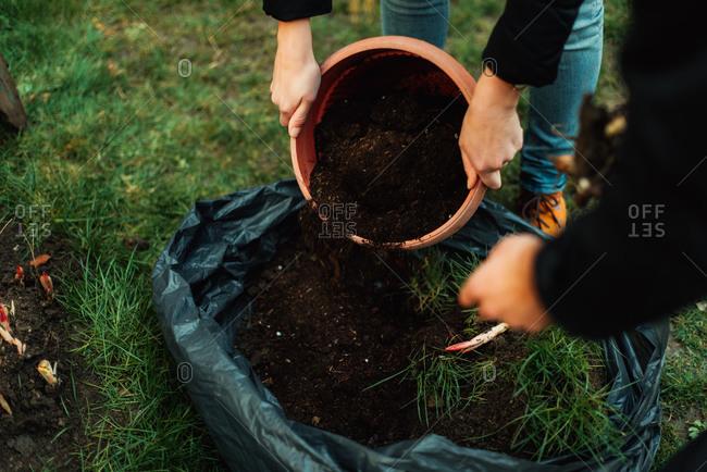 Woman dumping dirt out of a pot