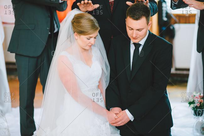 Couple kneeling in marriage ceremony