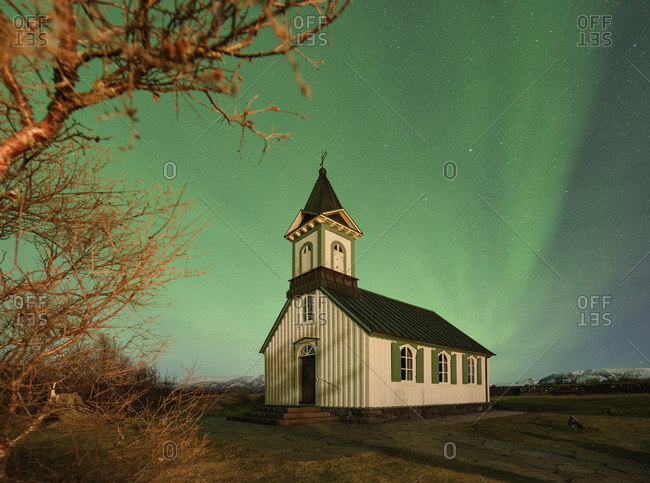 Country church in Iceland with the northern lights glowing brightly in the sky