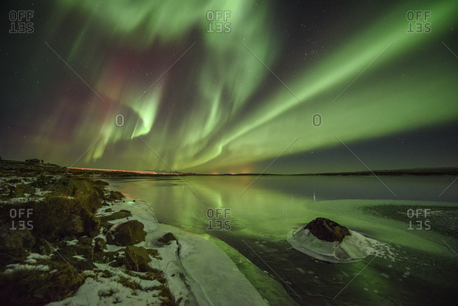 The northern lights reflecting in a lake in the Icelandic wilderness