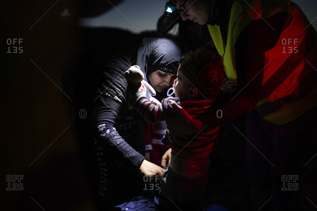 Lesbos, Greece - October 9, 2015: A mother changing her daughter's wet clothing on the Greek island of Lesbos after crossing the Aegean Sea from Turkey
