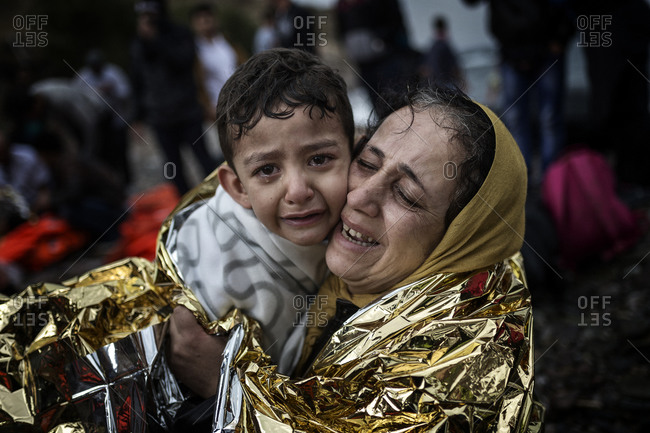 Lesbos, Greece - October 11, 2015: A mother and child in tears embracing each other on the Greek island of Lesbos after crossing the Aegean Sea from Turkey