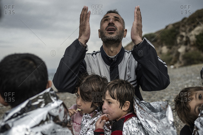 Lesbos, Greece - October 11, 2015: Man surrounded by children raising his hands in prayer on the Greek island of Lesbos after crossing the Aegean Sea from Turkey