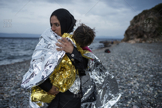 Lesbos, Greece - October 11, 2015: A mother and child embracing each other on the Greek island of Lesbos after crossing the Aegean Sea from Turkey