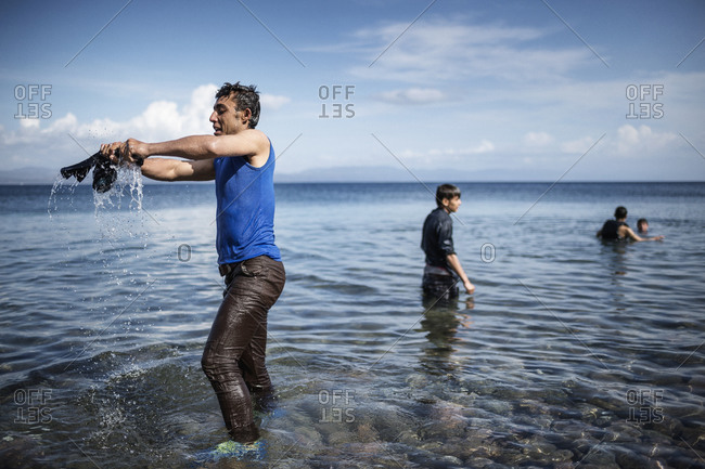 Lesbos, Greece - October 12, 2015: Man wringing water from clothing on the Greek island of Lesbos after crossing the Aegean Sea from Turkey