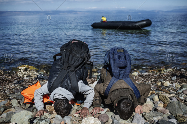 Lesbos, Greece - October 13, 2015: Two men wearing backpacks bow in prayer on the Greek island of Lesbos after crossing the Aegean Sea from Turkey