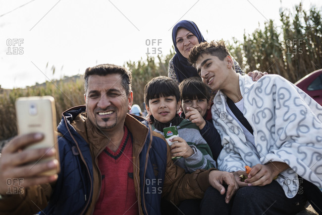 Lesbos, Greece - October 14, 2015: Refugee family taking selfie on the Greek island of Lesbos after crossing the Aegean Sea from Turkey
