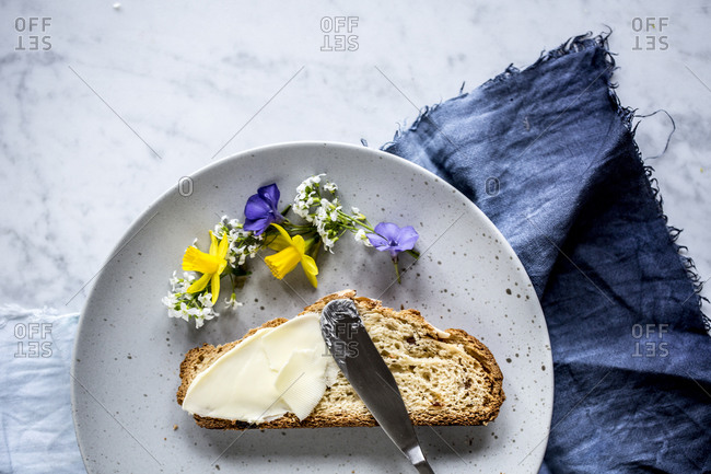 Overhead view of plate of slice of bread with butter and spring flowers
