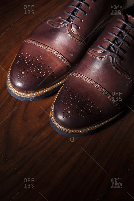 Men's dark brown brogues with mahogany background