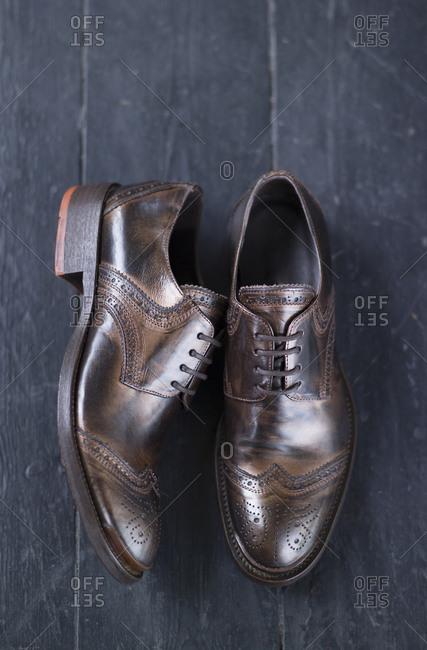 Men's dark brown brogue on black floorboards