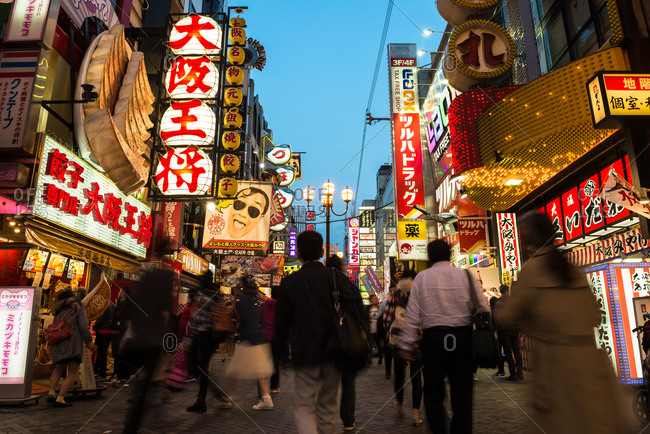 Osaka, Japan - March 30, 2016: People walking along a busy street lined with neon signs at dusk in Japan