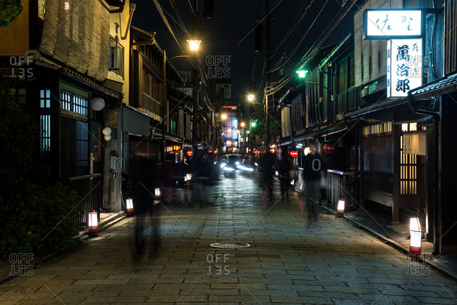 Kyoto, Japan - April 2, 2016: Silhouette of people walking along a street at night in Japan