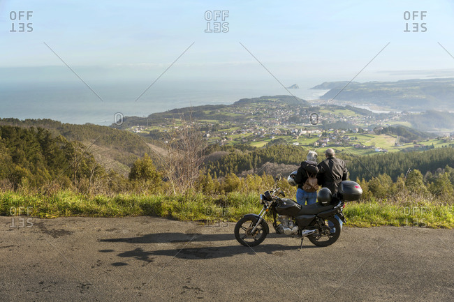 Couple standing by motorcycle enjoying the view from a cliff