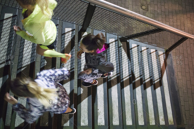 Overhead view of three women running up stairs during night workout