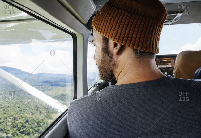 Man looking out window of small plane