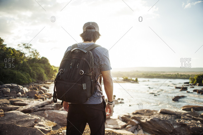 Man with backpack standing on rocky lake shore