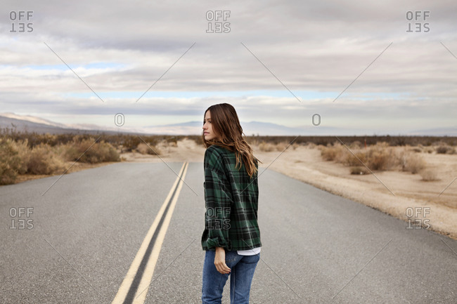 Young woman walking down a desert road