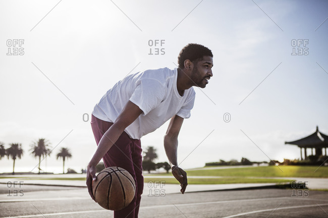Young man dribbling a basketball low to the ground