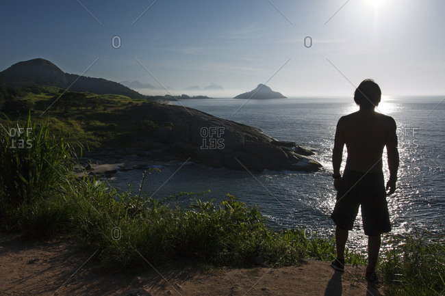 Silhouette of a young athletic man looking at the ocean