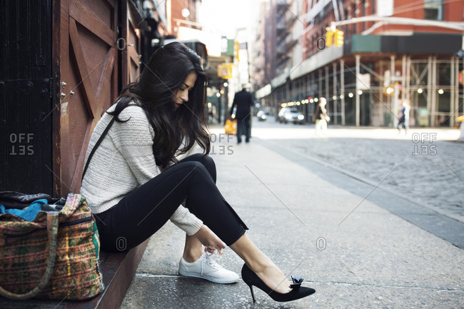 Young woman changing from high heels into sneakers
