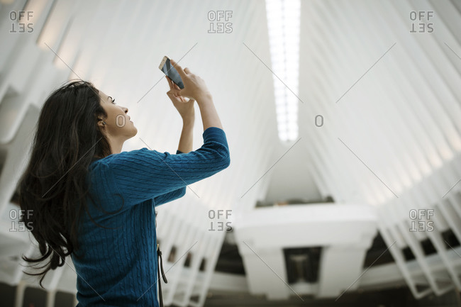 New York City, NY - March 10, 2016: Woman taking picture of a ceiling inside the World Trade Center Transportation Hub