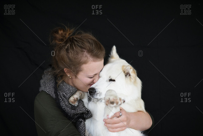Woman hugging her white dog